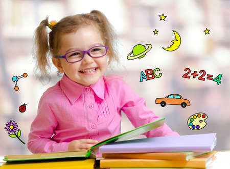 Happy child girl in glasses reading books in library photo