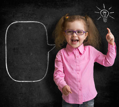 prodigy: Happy kid girl in glasses with bright idea standing near school blackboard in classroom
