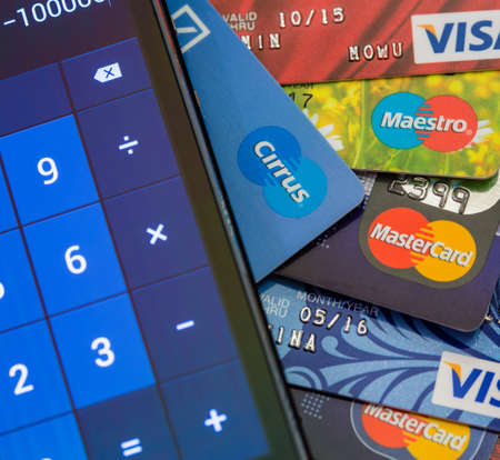 maestro: TOMSK, RUSSIA - JUNE 03, 2014: Calculator lying on table over pile of different credit cards: Visa, MasterCard, Cirrus, Maestro.