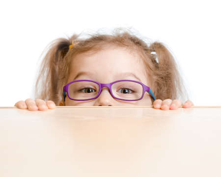 Funny girl in eyeglasses hiding behind a table photo