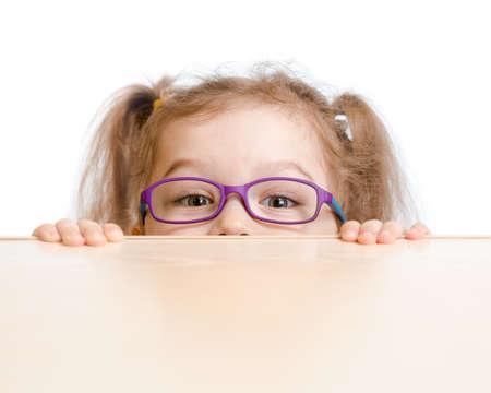 hyperopia: Ragazza divertente in occhiali da vista nascondersi dietro un tavolo Archivio Fotografico