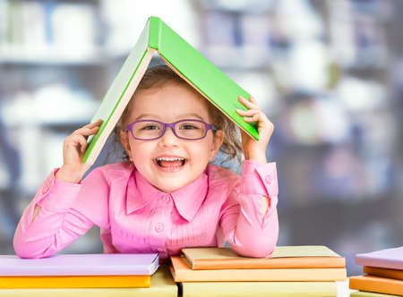 Little girl in glasses under roof made from book