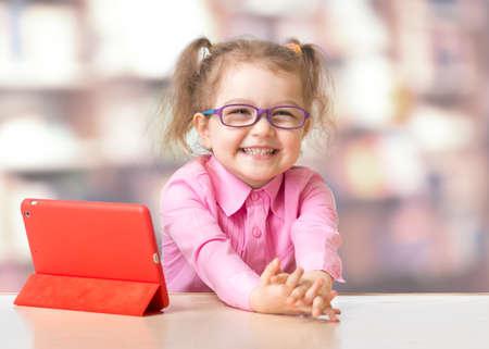 Kind zit met tablet-computer in de kamer