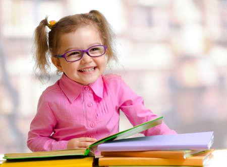 hyperopia: Ragazza felice del bambino in occhiali da vista lettura di libri, seduto al tavolo