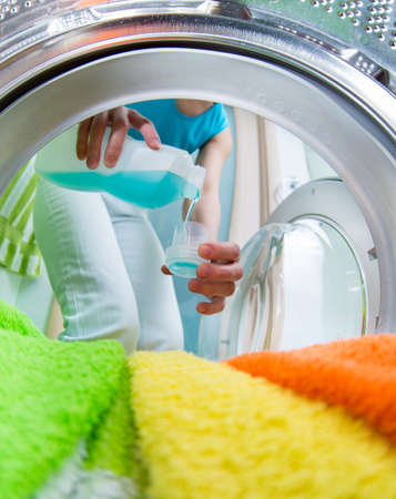 detergents: householder woman using conditioner for  washing machine
