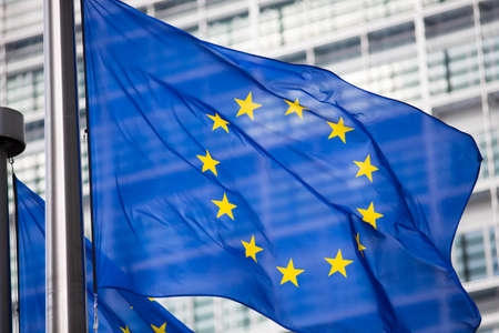 europe closeup: EU flag in front of Berlaymont building facade
