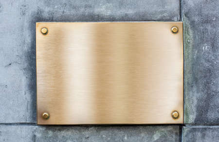 Golden plate or plaque made of bronze on vintage wall