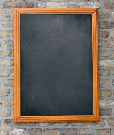 Aged blackboard hanging on brick wall as a background for your menu photo