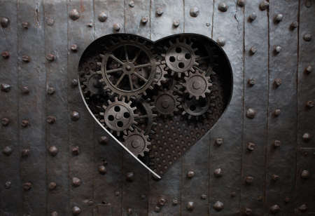 heart hole in old metal with gears and cogs photo