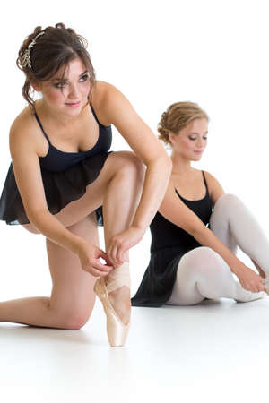 Two beautiful young girls preparing for dance training together isolated photo