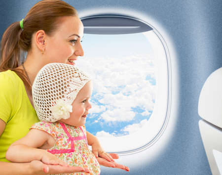 aeroplane: Happy mother and kid travelling together in airoplane cabin near window Stock Photo