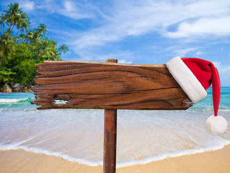 Christmas on beach concept. Wooden signboard with Santas hat. photo