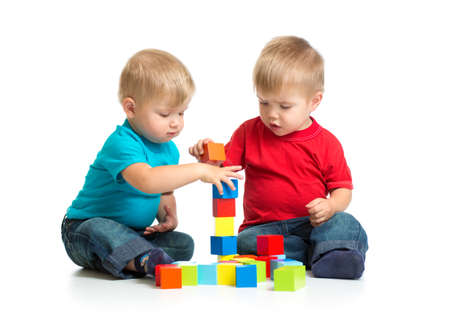 blocks: Two kids playing wooden blocks together building tower Stock Photo