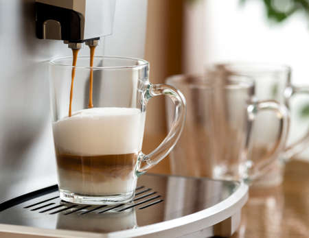 cappuccino coffee preparing in glass cup with help of machine