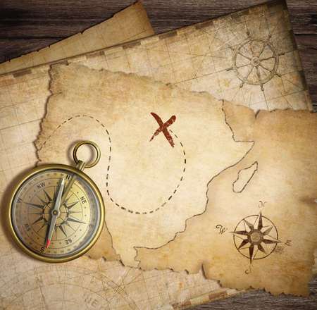 aged brass nautical compass on table with old treasure maps photo