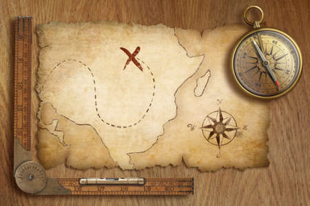 wooden table top view: aged treasure map, ruler and old gold compass on wooden table top view