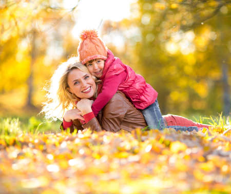 Parent and kid lying together on falling leaves. Happy family outdoor in autumn park. Smiling child is on mothers back. photo