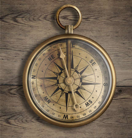 old compass: old brass compass on wood table close up