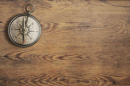 old compass on vintage wooden table top view photo