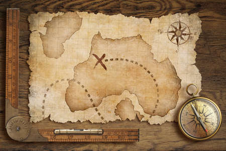 navigation map: aged treasure map, ruler and old bronze compass on wooden table top view