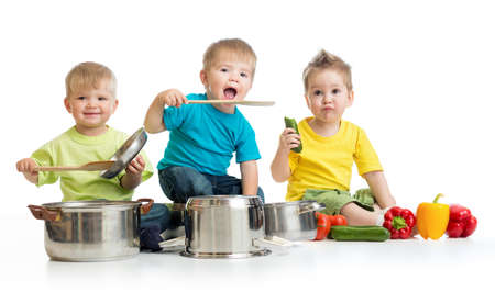 Kids group playing with pans and food isolated on white photo