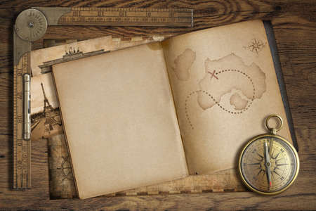 Vintage treasure map in open book with compass and old ruler