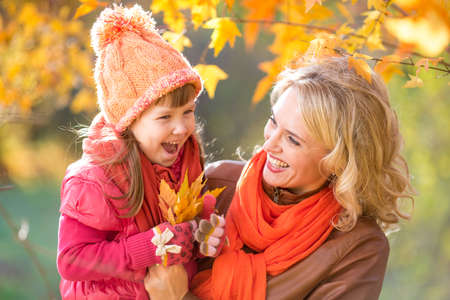 Happy parent and kid holding autumn yellow leaves outdoor. photo