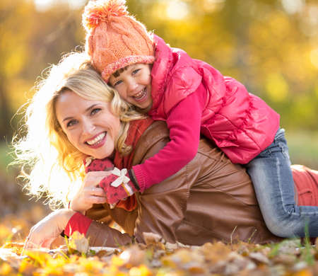 Parent and child lying together on falling leaves. Family outdoor in autumn park. Happy kid is on mothers back. photo