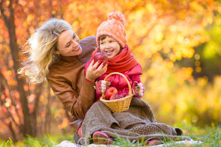 Mother and kid making pinic together in autumn park. photo