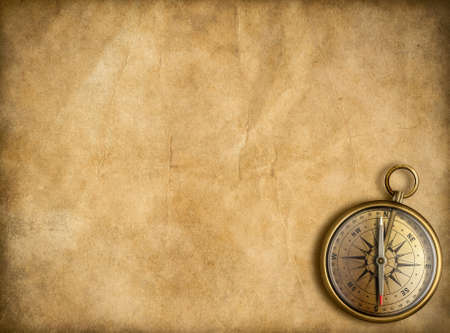 old golden compass with vintage map background photo