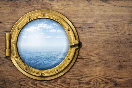 ship porthole on wooden wall photo