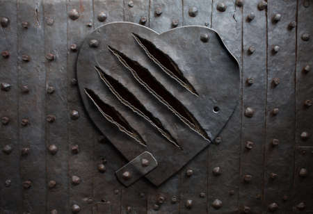 wounded heart: old metal heart with claw damage as metaphor Stock Photo