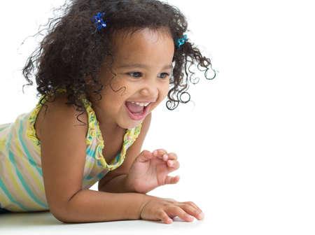 one little girl: Happy kid girl lying on floor and playing isolated on white