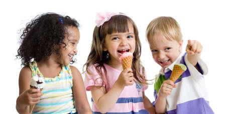 ni�os comiendo: felices los ni�os comiendo helado en el estudio aislado en blanco Foto de archivo