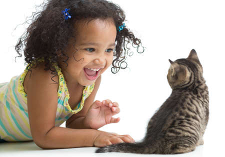 Happy kid girl lying on floor and playing with kitten isolated on white photo