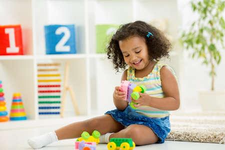 playing: Kid ni�a jugando juguetes en el hogar o el jard�n de infantes Foto de archivo