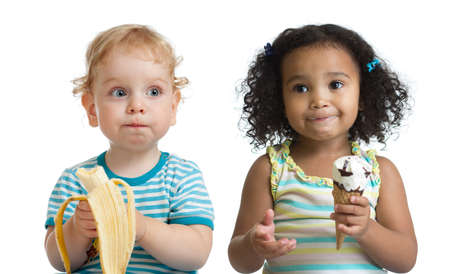 Two kids boy and girl eading fruit and ice cream isolated on white
