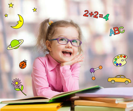 Happy child girl in glasses reading books in library