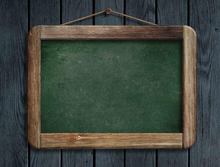 Aged green menu blackboard hanging on wooden wall photo