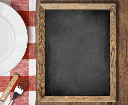 Menu chalkboard top view on table with plate, knife and fork photo
