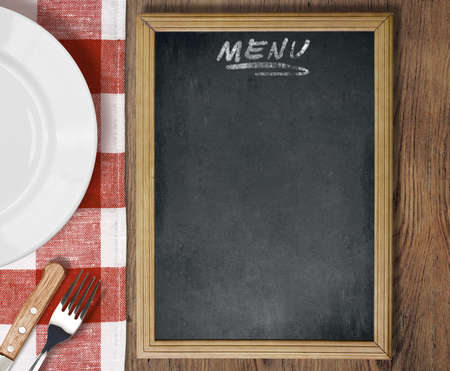 Menu chalkboard top view on table with dish, knife and fork photo