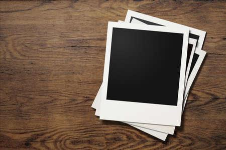 polaroid photo frames on old wooden background