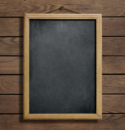 Aged menu blackboard hanging on wooden wall