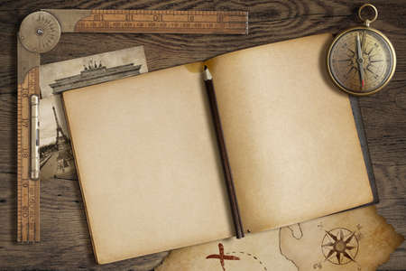 Open blank diary with map, pencil and compass photo