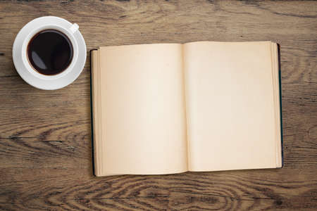 open book and coffee top view on table photo