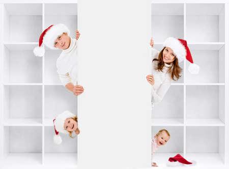 niños con pancarta: Navidad en familia en los sombreros de Santa con estantes