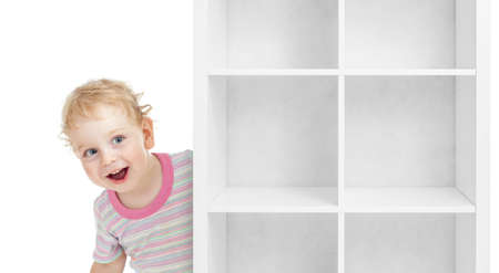 curly headed: Adorable kid boy behind empty white shelves isolated Stock Photo