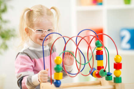 hyperopia: Kid in eyeglases playing colorful toy at home Stock Photo