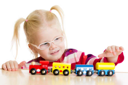 poor eyesight: Kid in eyeglases playing toy train isolated on white