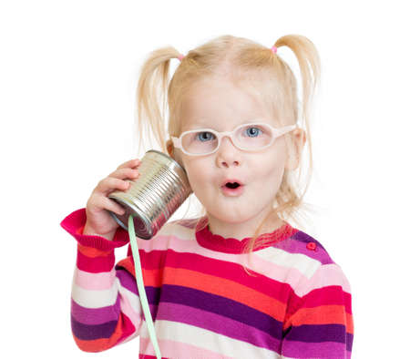 communication concept: Funny child in eyeglasses using a can as a telephone isolated on white